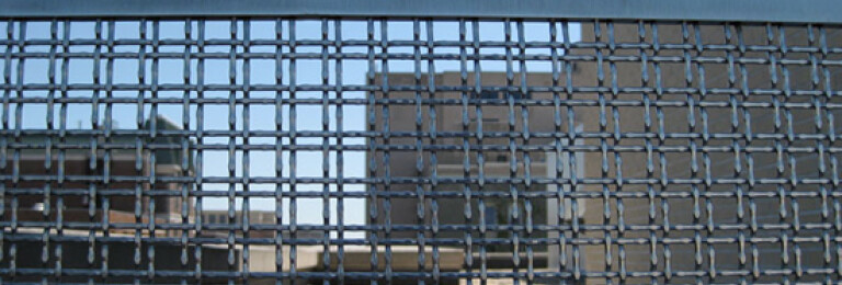 Stainless steel architectural wire mesh panels screen areas and define spaces.
