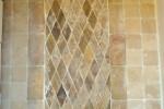 Antique tile rug in a bed of travertine tiles