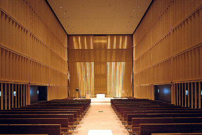 Behind the altar, a semi-transparent wall made of woven wire mesh from GKD, on which the shape of a cross is traced, radiates a gentle, luminous aura.