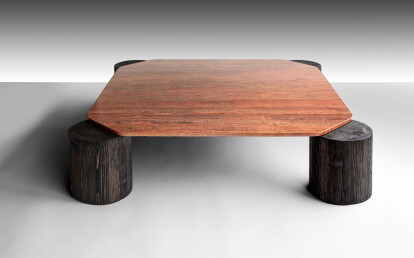 The Flame Red Travertine top of the Magnifico coffee table straddles the muscular Larch timber legs, effecting a beautifully bizarre and primitive cosmic landing pad.