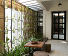 Invigorated with re-used furniture, and a green wall composed of glass bottles, the studio articulates shades of natural light as the central theme of its design.
