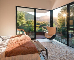 Huge walls of glass allow copious amounts of Southern California natural light into the master bedroom.