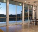 An incredible array of floor-to-ceiling Western Window Systems windows frames beautiful nighttime views of the Austin outskirts.