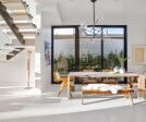 Large windows connect the dining area to the home's outdoor spaces.