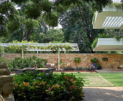 Formal Living Verandah : Wooden deck. pergola with creepers, gokak stone wall in background