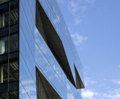 When viewed from the southeast corner of the building, the interaction between the undulating sections bring dynamism and deep shadows along the shifting harbor waters.