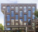 """Deep set windows used over the rest of the building are arranged in a vertically-oriented, """"running-bond"""" pattern, minimizing the horizontality of the office floor plates and providing visual interest and scale."""