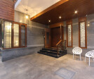 The entry looks prominent with stone cladding and unique outdoor furniture. False ceiling with lights forms a unique pattern. Pendant lights bring in a wealth of warmth with opulent metallic grills.