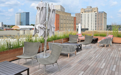 Roof deck planters anchor wood and glass parapet screen walls BBQ and socializing area atop a historic warehouse residential conversion