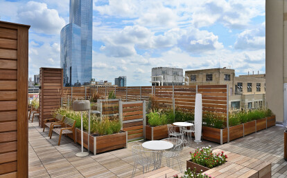 Roof deck planters anchor a large wood and glass screen wall enclosure for a roof top dog park with gates