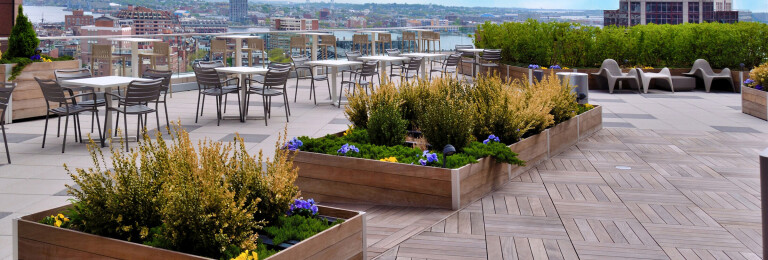 DeepStream's custom cost-effective, multi-section commercial wood planters create the landscaping foundation for an exclusive building amenity high above Boston's harbor without requiring roof penetrations.