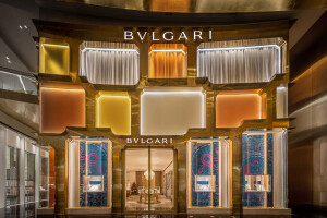 MVRDV frames colored glass in an asymmetric brass pattern for Bulgari Bangkok storefront