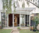 Glazed sliding doors open to the rear garden and to the courtyard, creating a large, connected indoor/outdoor space bookended by greenery.