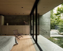 The master suite features a Series 600 Window Wall connected to a Series 980 Pivot Door that opens onto an outdoor space.