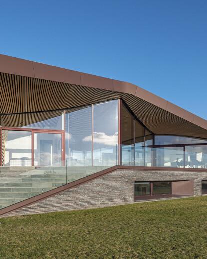 Inhabitable sculpture wrapped in an undulating roof frames Danish ocean views