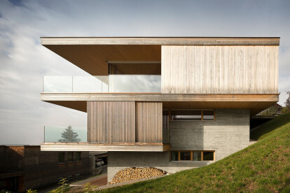 Light and transparent House K elegantly navigates a steeply sloping Austrian site